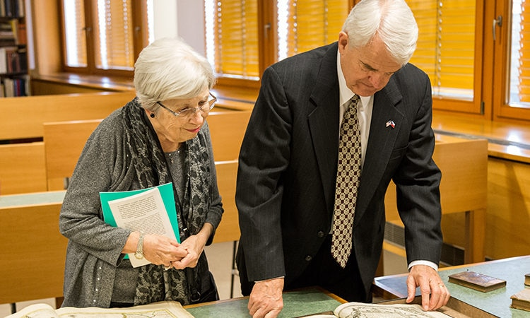 Ambassador King and Mrs. King look at collection of ancient maps at the Moravian Library.